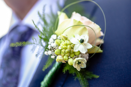 Cheerfully made up corsage with bright flowers. Groom with floral ornament for a wedding. Traditional wedding details for bride, brides sum and guests Foto de archivo - 103920162