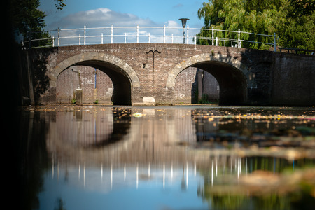 Masonry brick old bridge with a white wrought iron railing. Atmospheric photo of historical waterworks in the old hanseatic city of Kampen in Overijssel, the Netherlands. Bridge reflecting in the water surface with long floating cumulus clouds