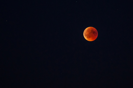 Moon in the starry sky with a blood red color as a result of a lunar eclipse through the earth.