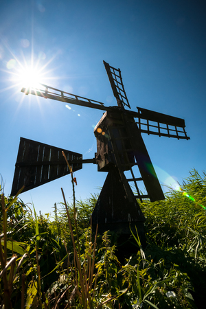 Characteristic black tarred windmill between green reeds at the edge of a grassland and waterways. Unique Dutch landscape photo with cultural heritage in the Dutch landscape on a sunny day under a blackened sky with backlit sunlight Standard-Bild