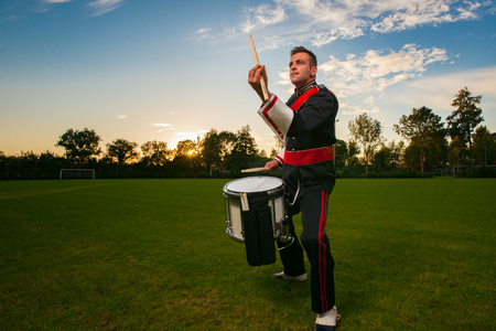 Percussion player or drummer during an outdoor photo shoot with studio lamps in an attractive interactive evening scene Stock Photo