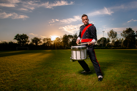 Percussion player or drummer during an outdoor photo shoot with studio lamps in an attractive interactive evening scene
