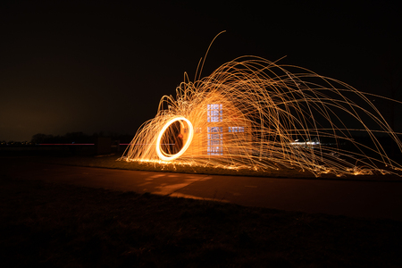 Rotating steel wool with sparkling burning sparks in the night with long exposure shutter photographed in different variations Banco de Imagens