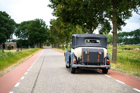Old luxury wedding car driving in a Dutch polder landscape