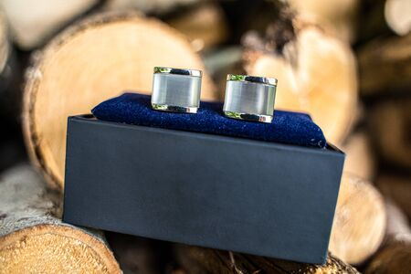 Silver cufflinks in a luxurious black box with velvet blue trim and a natural background of firewood Stock Photo