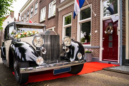 Classic old-timer in original condition driving through the streets of an old Dutch village