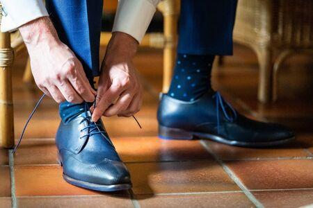 Der Mann trägt Schuhe. Binden Sie die Schnürsenkel an den Schuhen. Herrenstil. Berufe. Zur Vorbereitung auf die Arbeit, zum Meeting.