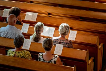 People in wooden benches in dutch church reading the holy literugie and singing psalms