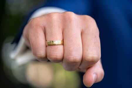 Newlyweds reach out their fists with wedding rings Imagens
