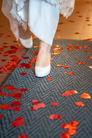 Bride with pumps walks on carpet with red paper hearts made of confetti Standard-Bild - 129650102