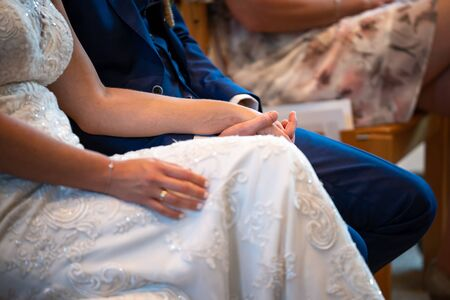 Bride and groom holding their hands during beautiful wedding ceremony in church, indoors.