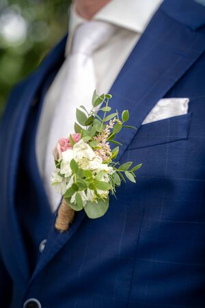 Detail view from of groom with floral ornament on a three-piece groomsuit