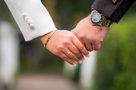 Closeup of loving couple holding hands while walking in te street of dutch town· Young couple in love walking in the  park holding hands 스톡 콘텐츠