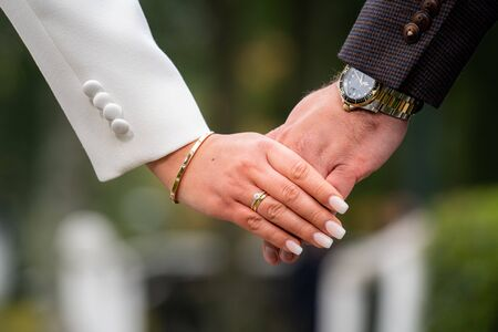 Closeup of loving couple holding hands while walking in te street of dutch town· Young couple in love walking in the  park holding hands