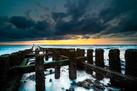 Breakwater formed of wooden panels on a beach at stormy weather with sunset along the coastline of zeeland, Netherlands Foto de archivo