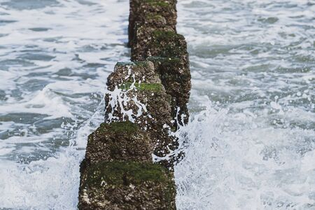 Sea wave overflowed through a wooden groyne next to the beach.