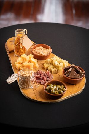 Overhead photo of a selection of cheeses, shot taken on a boat with rustic texture and maritime details