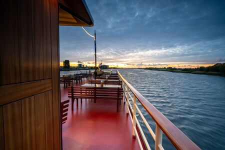 View over a river in the dutch delta, cloudy sky with sunset from the top deck of a tall ship