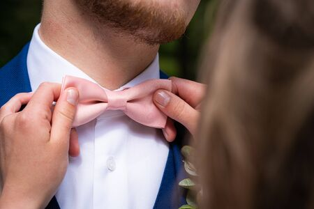 Bow tie in pink color of groom with a blue suit and a white bluze, bride does loving gesture, detail wedding Foto de archivo - 150218562