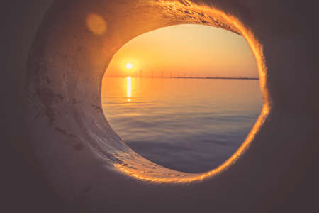 Sunset glowing through Close up of anchor hawse hole on an old boat with abstract look