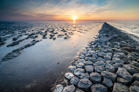 Mud flat of the 'waddenzee' during low tide under scenic dramatic sunset sky with clouds