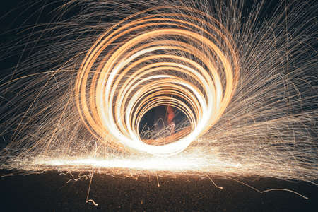 Steel wool photography involves setting light to steel wool and then spinning it in the air to create sparks that light up the dark night sky, creating patterns of light during a long exposure. 免版税图像