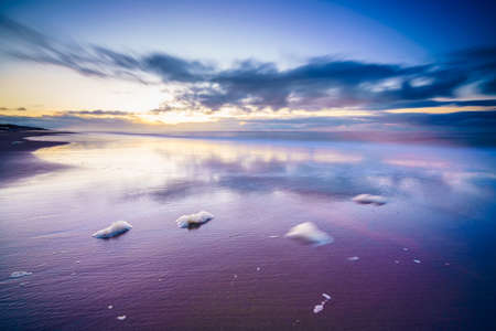 Maritime landscape at sunset with reflection of clouds in low tide water, Waddenzee, Texel, The Netherlands
