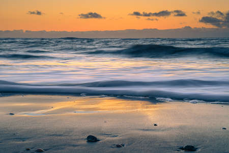 Peaceful and tranquil zen-like sunset on the beach with beautiful reflections on the water - North Sea, Netherlands 免版税图像