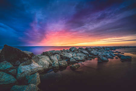 Breakwater of large rocks in the Ijsselmeer near the town of Urk in the province of Flevoland during a dramatic sunset with great clouds and colors