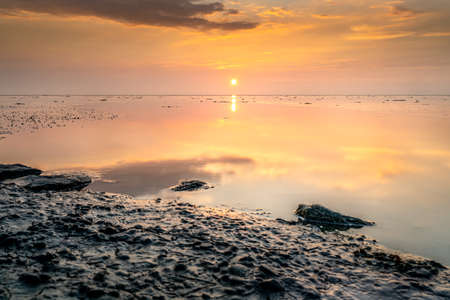Tranquil and tranquil zen-like sunset on the beach with beautiful colors in pink and red with reflections on the water - Wadden Sea, Netherlands 免版税图像