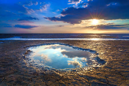 Wadden Sea in the Netherlands during sunset with wide angel view and colorful clouds.
