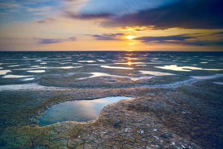 Beautiful summer. Sea coast spangled by stone, the sunrise is reflecting on the wet sand. Morning landscape.