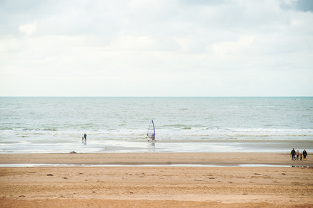 Surfing on the beach in front of waves at autumn with some people walking by