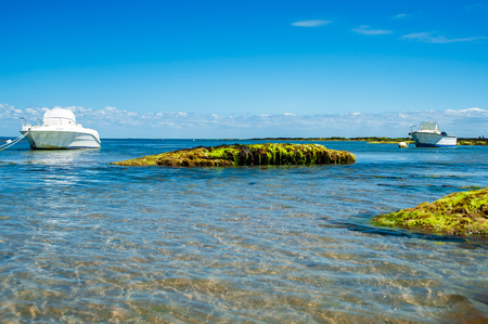 two boats floating near the beach on water with rocks in summertime on the isle of Noirmoutier