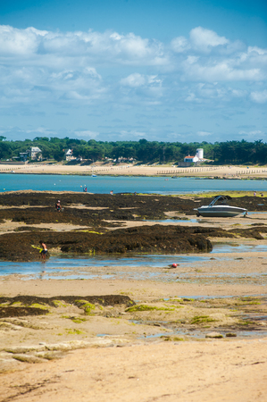 view on the beach of le petit vieil on the isle of Noirmoutier in summertime with some people on it