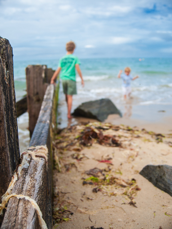a wooden bar leading into the sea with some kids playing in the sea in summertime Banque d'images