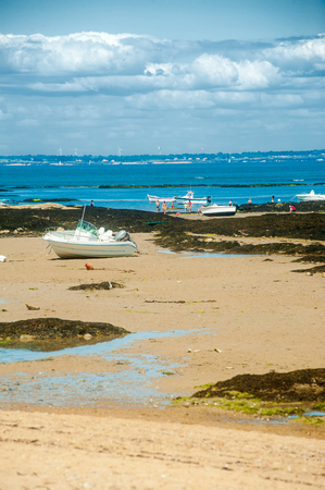 Boat on the beach of le plage du petit vieil at Noirmoutier in summertime with people fishing in the background Stock fotó