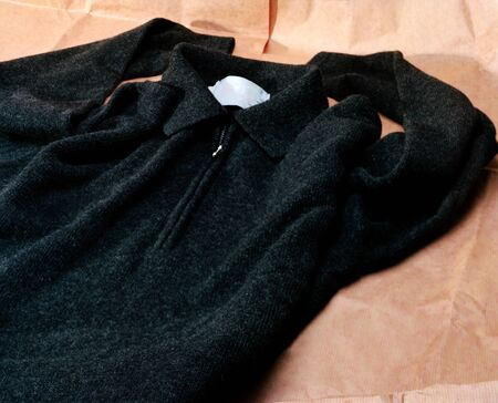 a black sweater laying  on brown wrapping paper