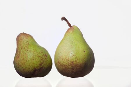 Two pears standing in front of a white background