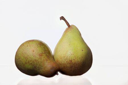 Two pears on a white background with one pear standing and the other one laying