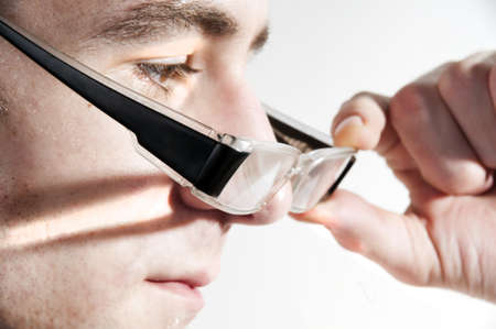 young man removing black glasses from face photo