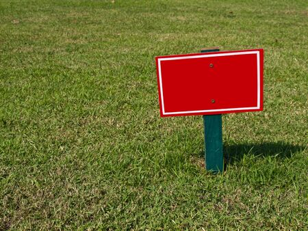 red sign on grass photo