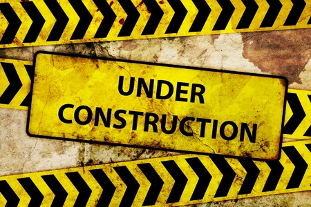 dangerous construction: rusty under construction sign  Stock Photo