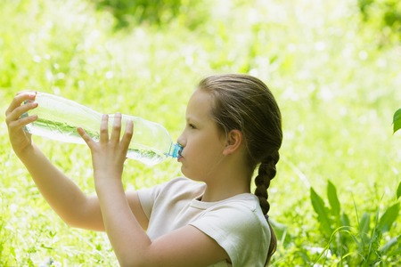water quality: Girl child drinks water from a bottle outdoor