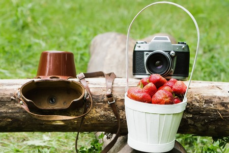 Old camera with a basket of strawberries