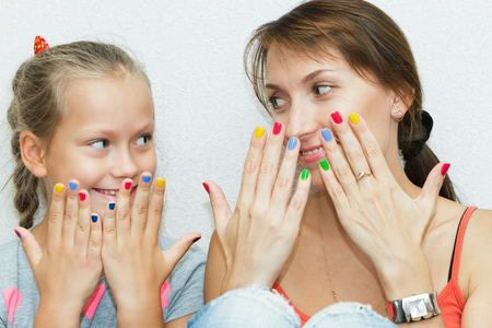 Hands of mother and daughter manicure
