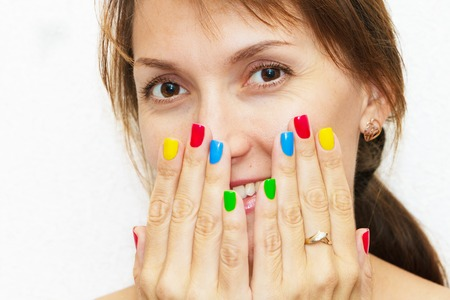 Portrait of a girl with hands and a multi-colored manicure. Reklamní fotografie - 121647304
