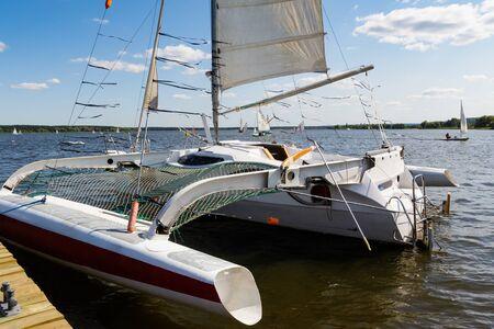 Moored catamaran with sail, regatta