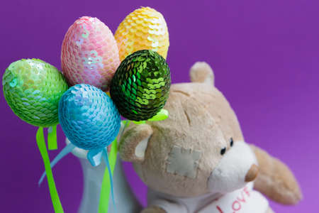 Easter eggs with a teddy bear on a colored background.