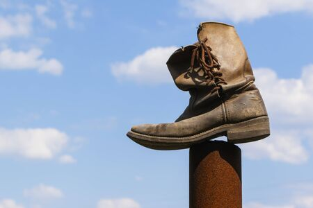 Old working leather boot on sky background 版權商用圖片 - 141690799